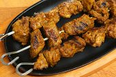 Chargrilled Indian lamb tikka kebabs in authentic sizzler serving dish.