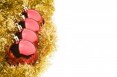 Four Red Christmas Balls In A Row Over Gold Tinsel Garland, Isolated On White Background