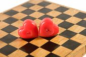 Heart-Shaped Candles On An Old Chessboard