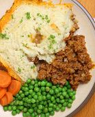 Shepherd's pie served with peas and carrots.
