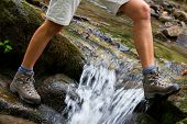 stock photo of crossed legs  - Hiking boots - JPG