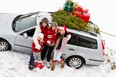 Waiting for Christmas  - the family is carrying  Christmas tree and gifts on the roof of the car