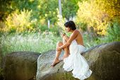 pic of naturist  - nude woman sit with a cigareton stones against nature background - JPG
