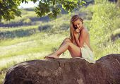 stock photo of naturist  - Beautiful nude woman sit on stones against nature background - JPG
