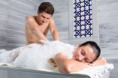 Male bath attendant massages and bathes adult woman at Turkish bath