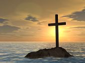 Concept or conceptual dark christian cross standing on a rock in the sea or ocean over a beautiful s