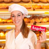 Female baker or saleswoman in her bakery selling fresh bread, pastries and bakery products, she hold