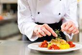Weiblich-Chef in Hotel oder Restaurant Küche kochen, nur Hände, sie ist ein Gericht auf Teller beenden
