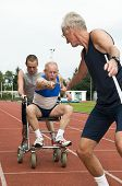 stock photo of helping others  - Disabled person and his helper reaching for an other athlete to pass him the baton - JPG