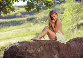 pic of naturist  - Beautiful nude woman sit on stones against nature background - JPG