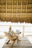 Young man sitting with laptop underneath thatch roof on the beach