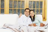 Couple sitting on the couch under a blanket together