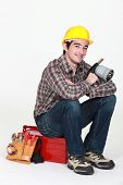 Tradesman holding a blowtorch and sitting on his toolbox