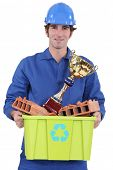 Builder with an award for recycling material