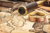stock photo of spyglass  - Vintage brass telescope on antique map - JPG
