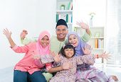 Happy Asian family at home. Muslim family having fun. Southeast Asian parents and children open arms