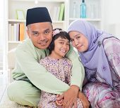 Muslim parents hugging child. Southeast Asian Malay family lifestyle. Happy smiling father mother an