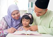 picture of malay  - Malay Muslim parents teaching child reading a book - JPG