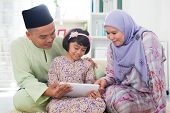 Southeast Asian family using tablet pc computer at home. Muslim family living lifestyle. Happy smili