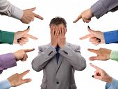 stock photo of bullying  - Hands pointing towards businessman holding head in hands concept for blame - JPG