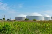 stock photo of hoppers  - A biogas plant under a blue sky - JPG
