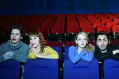 Four young scared and surprised people watch movie in cinema theater. Focus on girls.