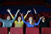 Four happy young friends sit in cinema theater and raise hands up.