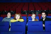 Four happy young people rest in movie theater. Focus on left girl.