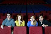 Four young friends look at screen in cinema theater and very much afraid.