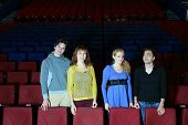 Four happy young friends stand in cinema theater and look in different directions.