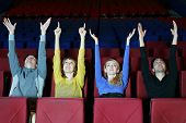 Four happy young friends sit in cinema theater and pull hands up.