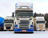 Three Long Haulage Trucks In Snowfall