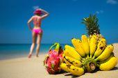 Tropical fruits and a woman in a bikini sunbathing on the beach on sea background. Idealistic scene