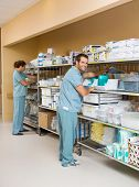 Full length of male and female nurses arranging stock on shelves in hospital storage room