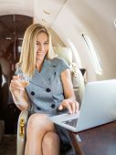 Happy businesswoman holding wineglass while using laptop in private jet