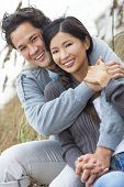 image of couple sitting beach  - Young Asian Chinese man  - JPG