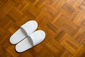 Pair Of White Slippers On A Wooden Floor