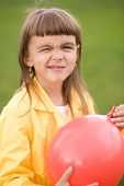 Little Girl Is Inflating Red Balloon