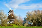 picture of windmills  - Traditional wooden windmill in a lush garden with four sails or blades turning in the wind to generate power and energy for farming or manufacture from the kinetic energy of the wind - JPG