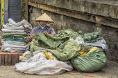 Woman Repairs Old Plastic Bags In The Street Of Hanoi.