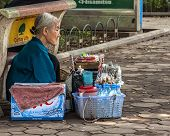 Old Woman Street Vendor Selling Water While Sitting On Her Haunches.