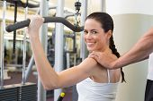 Fit brunette using weights machine for arms with trainer touching shoulders at the gym
