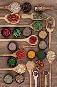Large spice and herb selection in wooden bowls, spoons and scoops over oak wood background.