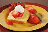 stock photo of pound cake  - Pound cake slices topped with fresh strawberriesnad whipped cream a summertime treat - JPG