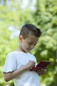Little boy playing with is video games outdoors
