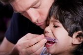 foto of physically handicapped  - Father helping his disabled son with medical mouth guard - JPG
