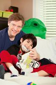 picture of babysitting  - Handsome father playing cars with disabled son on floor mat - JPG