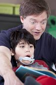 image of storytime  - Father reading book with disabled son - JPG