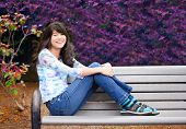Picture of young preteen girl sitting on park bench outdoors.