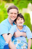 pic of babysitting  - Handsome father sitting with smiling disabled seven year old son outdoors - JPG